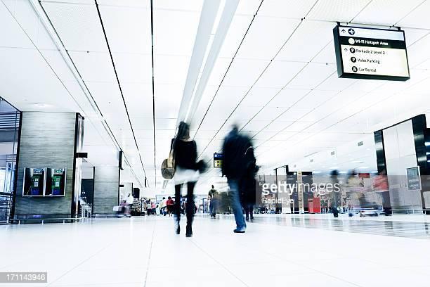 Couple hurry through airport concourse