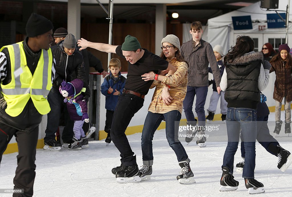 A couple ice skates at McCarren Park pool in New York,United States on December 24,2013 after McCarren Park pool converted to an ice skating area. Pool hosts 800 visitors everyday,without regard to cold weather American people have fun in McCarren Park pool in New York,United States on December 24,2013.