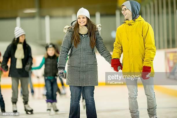 Couple ensemble le patinage sur glace à la patinoire