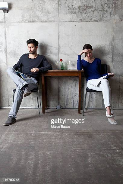 A couple ignoring each other while reading separate magazines