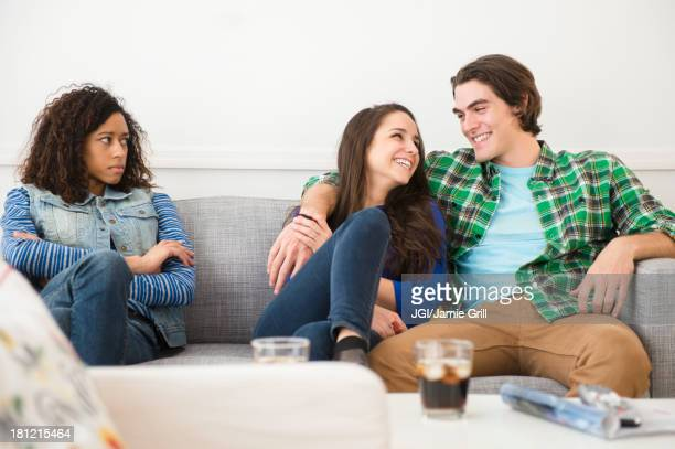 Couple ignoring friend on sofa