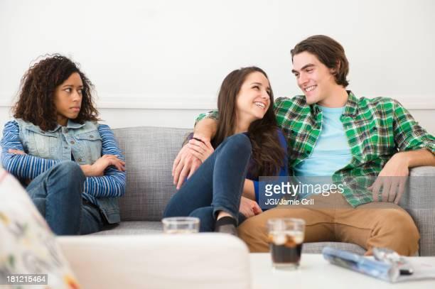 Couple ignoring friend on sofa