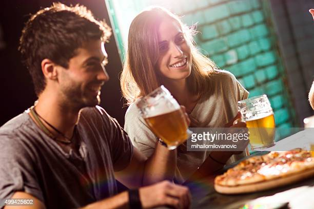 Couple in a bar, having fun with friends
