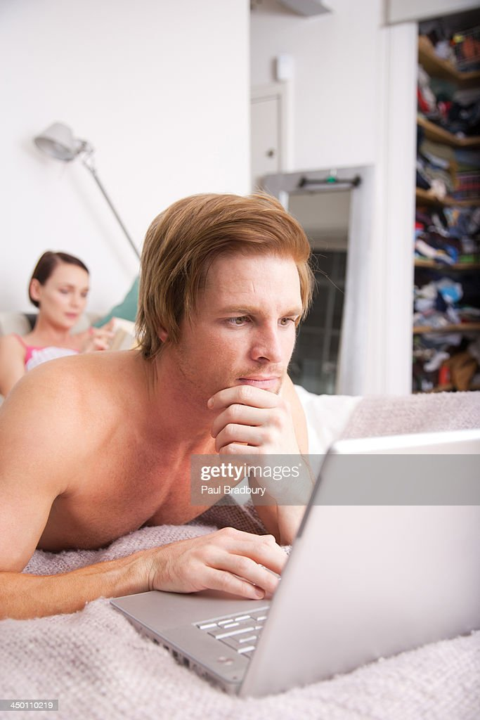 Couple in a bed with the woman reading and the man on a laptop : Stock Photo