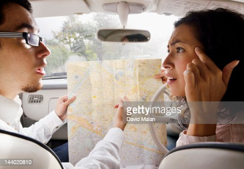 Couple in a car arguing over a map : Stock Photo