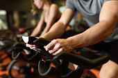 Close-up of hands of a man biking in the gym, exercising legs doing cardio workout cycling bikes. Couple in a exercising class wearing sportswear.