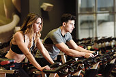 Two people biking in the gym, exercising legs doing cardio workout cycling bikes. Couple in a exercising class wearing sportswear.