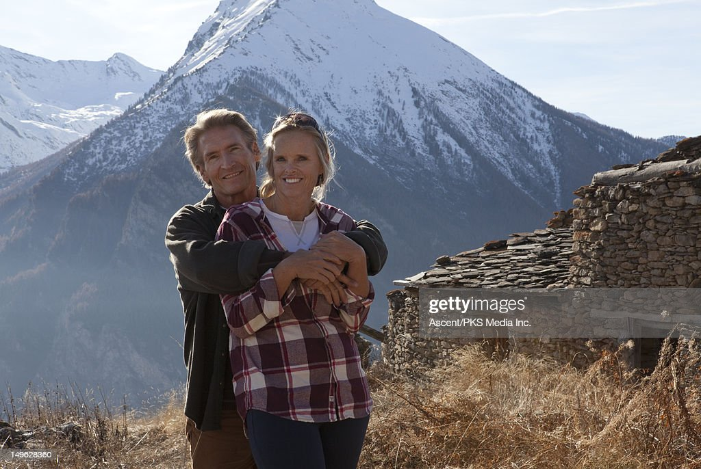 A couple in a mountain meadow beside a stone hut : Stock Photo