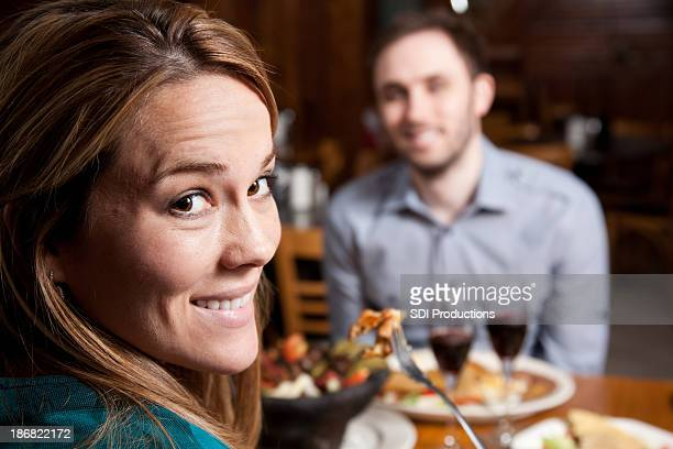 Couple in a restaurant smiling at dinner.