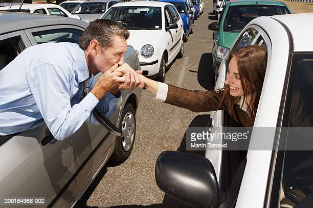 Couple in adjacent cars in traffic jam, man kissing woman's hand
