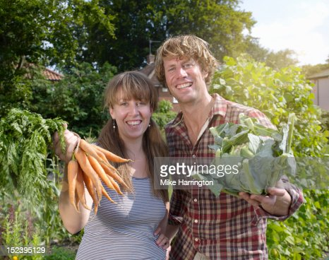 Couple in allotment posing with vegetables : Stock Photo