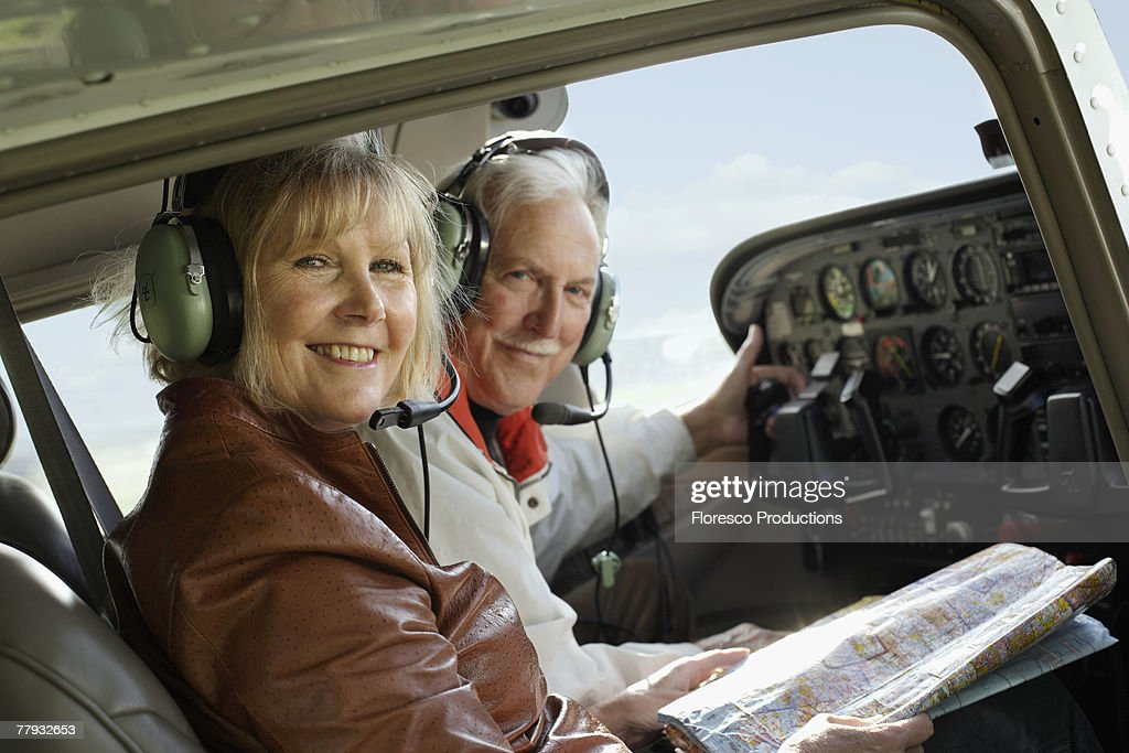 Couple in an airplane cockpit with a map : Stock Photo