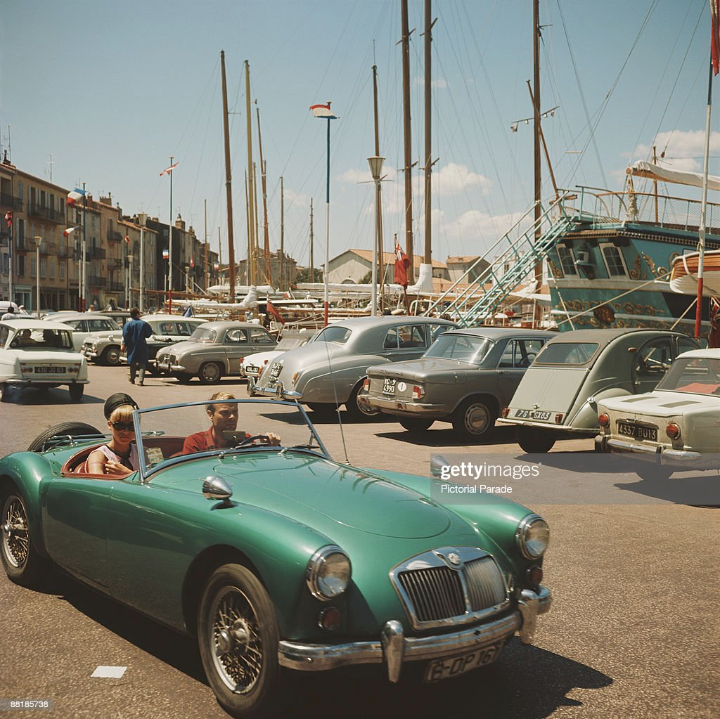 A couple in an MG sports car at the harbour in St Tropez France circa 1965