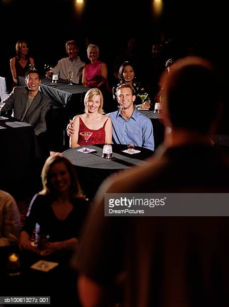 Couple in audience watching comedian, smiling