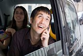 Couple in backseat of car on cell phone