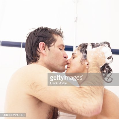 Couple In Bath Man Shampooing Womans Hair And Kissing Her On Nose