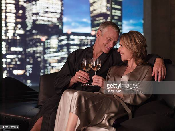 Couple in bathrobes drinking wine in living room at night