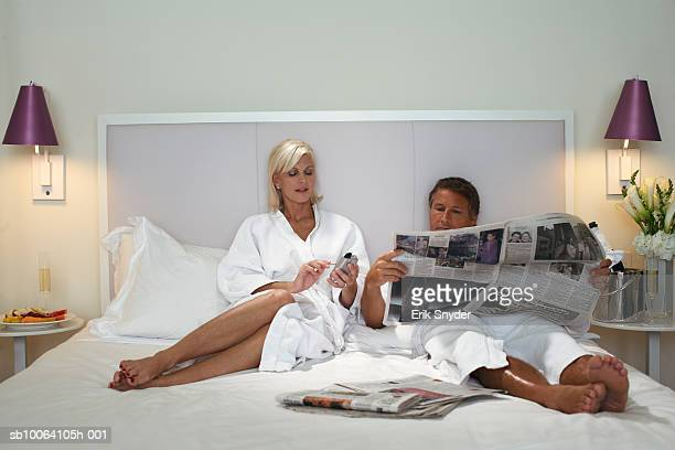 Couple in bathrobes relaxing on bed, man reading newspaper