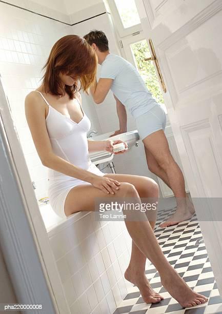 Couple in bathroom, man shaving, woman holding cream.