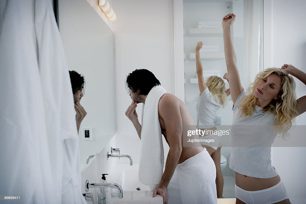 Couple in bathroom ,  woman stretching and man brushing teeth : Stock Photo