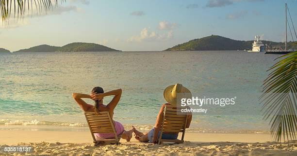 couple in beach chairs, playing footsie and watching sunset