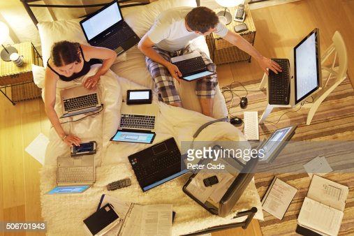 Couple in bed surrounded by computers