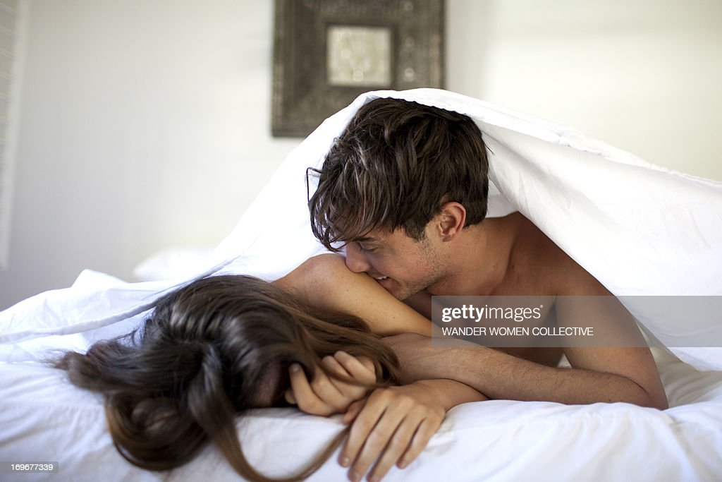 Couple in bed under white sheets kissing : Stock Photo