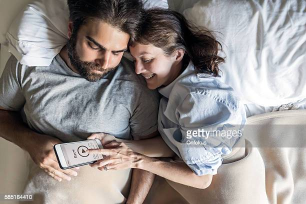 Couple in Bed Using Coffee Maker Application on Smart Phone
