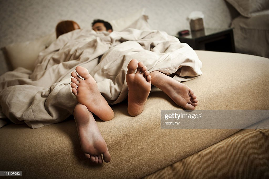 Couple in bed with feet hanging out the covers : Stock Photo