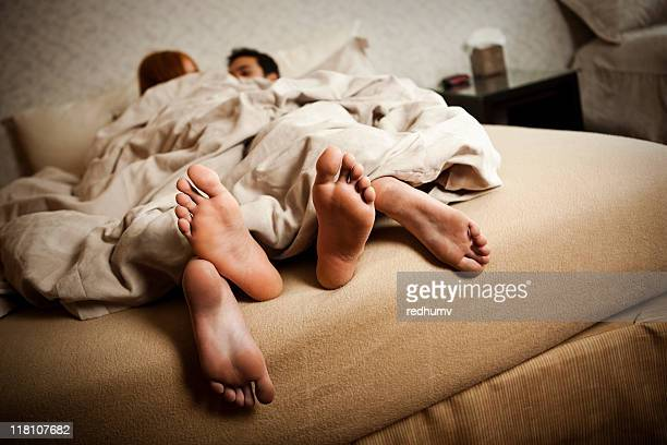Couple in bed with feet hanging out the covers