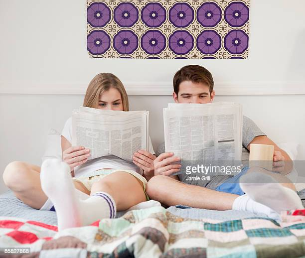 Couple in Bed with Newspapers