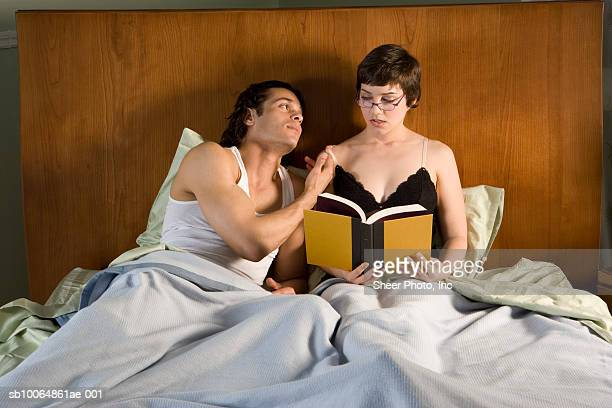 Couple in bed, woman reading book
