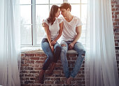Beautiful young couple at home. Hugging and kissing while sitting on a window sill. Enjoying spending time together.