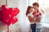 Beautiful young couple at home. Hugging, kissing and enjoying spending time together while celebrating Saint Valentine's Day with gift box in hand and air balloons in shape of heart on the background.