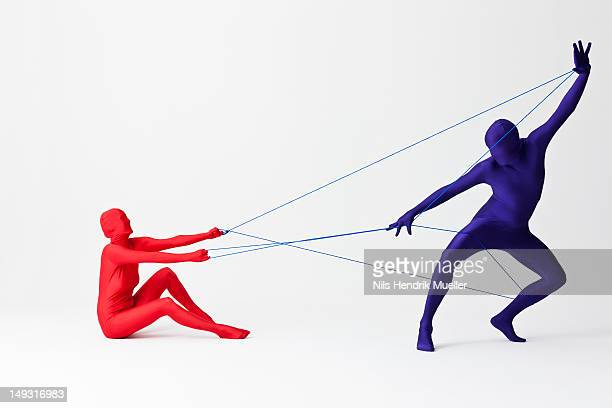 Couple in bodysuits playing with string