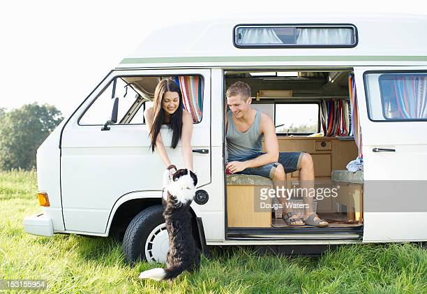 Couple in camper van playing with dog.