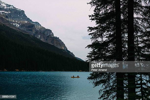 Couple in canoe on Moraine lake, looking at camera, Banff National Park, Alberta Canada