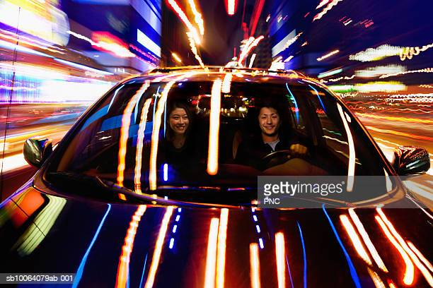 Couple in car at night, lights reflected on bonnet