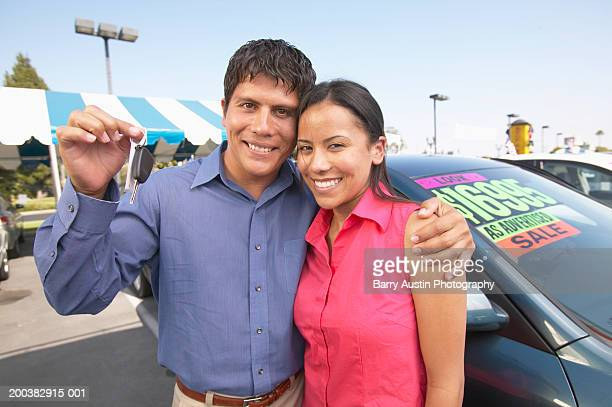 Couple in car lot, man with arm around woman's shoulder holding keys