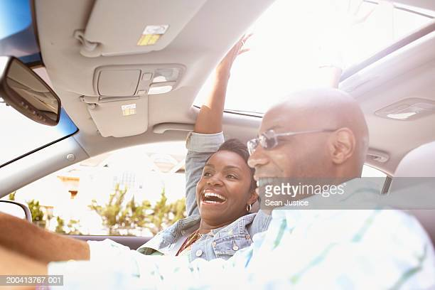 Couple in car sticking hands out of sun roof, side view, close-up