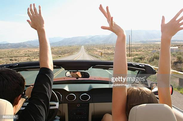 Couple in car with hands in air