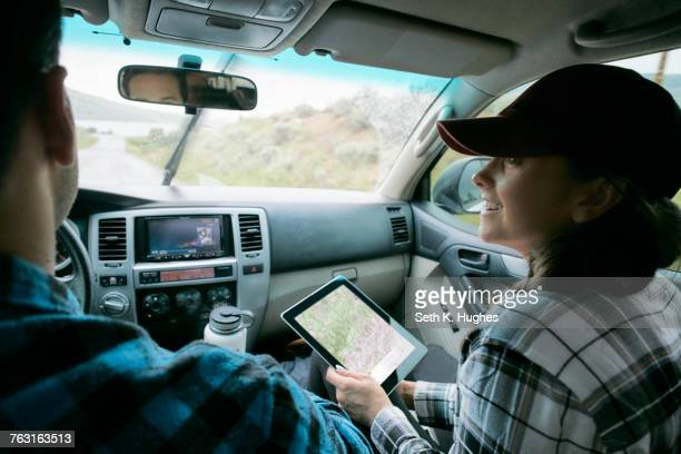 Couple in car, woman holding digital tablet with map showing