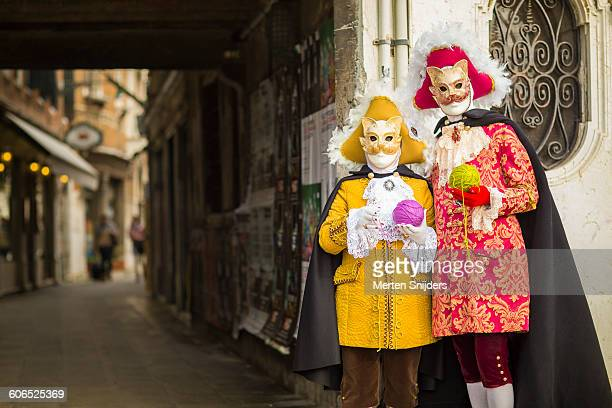 Couple in cat costumes with wool balls at alleyway