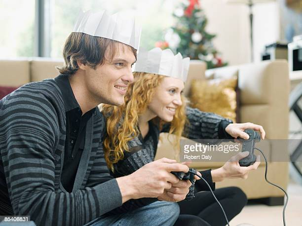 Couple in Christmas crowns playing video game