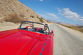 Couple in classic car on desert road
