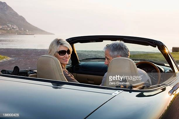 Couple in convertible admiring coastline