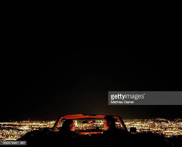 Couple in convertible overlooking city, rear view