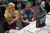 A couple in costume play a video game during the Video Gamers United convention on August 16 2014 at the Walter E Washington Convention Center in...