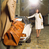 Couple in courtyard, man taking bag from boot of car