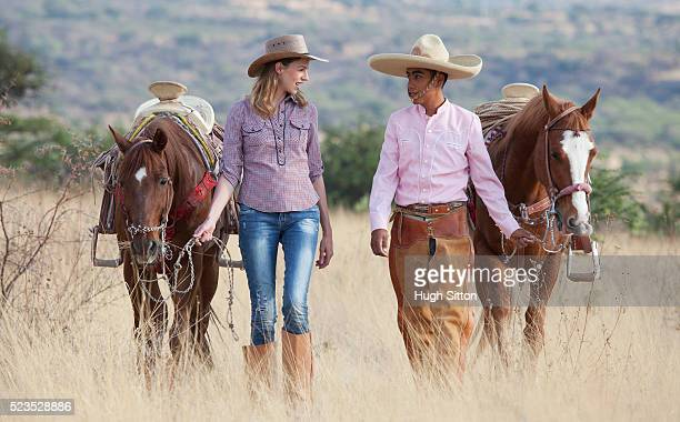 Couple in cowboy hats leading horses